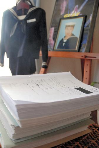 遺影と海上自衛隊の制服が飾られている自殺した男性の部屋。手前は、現役隊員の告発を受けて見つかったアンケートなど証拠書類