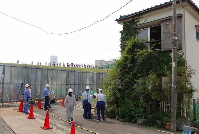 江戸川区土木部は、移転に同意しない地権者の家屋の強制撤去を開始した。反対地権者は堤防の上から「不要なスーパー堤防事業は中止せよ」等と書かれた横断幕を広げて抗議の声を上げた=2014年7月3日、東京都江戸川区北小岩