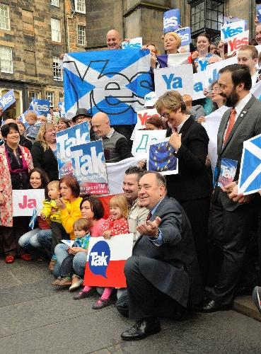 自治政府のサモンド首席大臣(最前列右端)と、各国の言葉で「イエス」と書かれたパネルを持つ支持者たち=9日、英スコットランド・エディンバラ