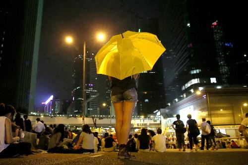 香港中心部で、デモのシンボルである雨傘を差して民主派の集会に参加していた女性