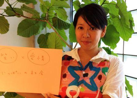 写真・図版 : 「『笑い』と『愛情』いっぱいの社会」という自身が目指す社会のフリップをもつ佐藤よし子さん。着ている服は、本文中で紹介されているダウン症の方がデザインしたフラボアのもの。