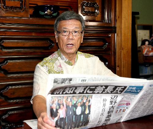 自身の当選を伝える沖縄タイムスに目を通す翁長雄志氏=2014年11月17日、那覇市