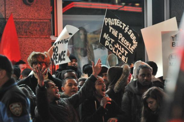 抗議する若者たち。「市民を守り、奉仕してくれ」と書かれたプラカードが見える=4日深夜、米ニューヨークのタイムズスクエア