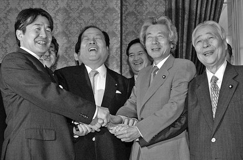 郵政民営化法案が成立し、握手する小泉純一郎首相ら=2005年10月、国会内