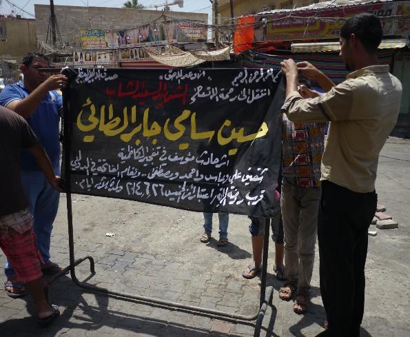 カードミヤで26日にあった自爆テロで死んだ若者の友人たちが、27日朝、爆発現場に若者の名前を書いた黒い幕を掲げた=川上撮影