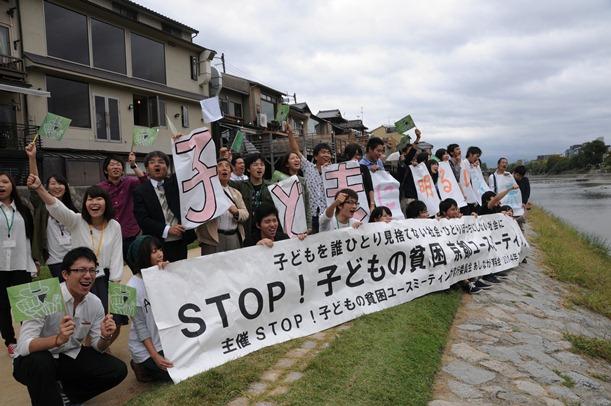 「子どもの貧困」をテーマにした集会のあと、鴨川の河川敷で通行人にアピールする大学生ら=2014年10月、京都市中京区