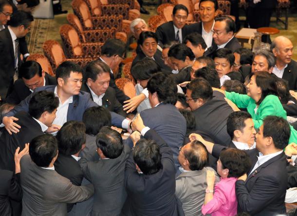参院特別委での安全保障関連法案の採決を巡り、もみ合う与野党の議員ら。中央奥は見守る安倍首相