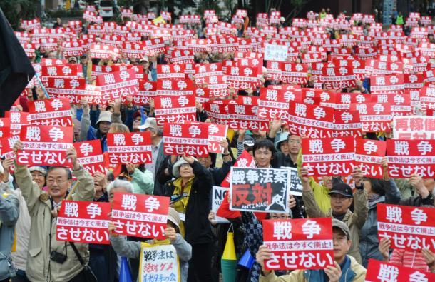 「戦争させない」と書かれたプラカードを掲げる参加者たち=2015年10月、札幌市中央区