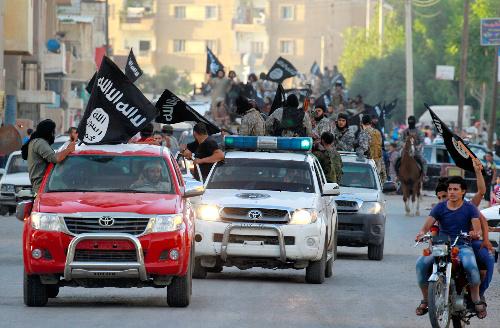 過激派組織「イスラム国」(IS)が「首都」と称するシリア北部ラッカで2014年6月、車列を組んでパレードする戦闘員ら=ロイター
