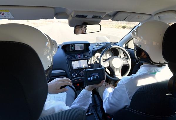 運転手がハンドルから手を離し自動運転するテスト車=2014年5月27日、北海道帯広市