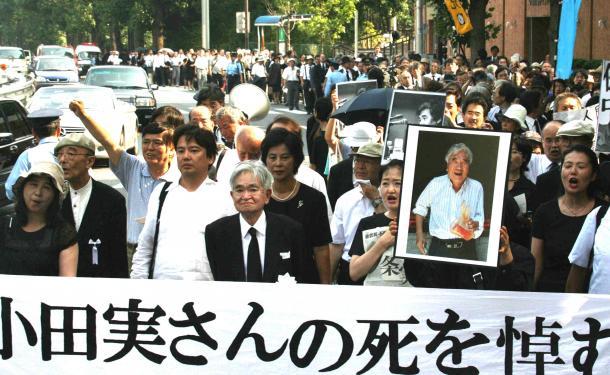 小田実さんの遺影と鶴見俊輔さんを先頭に追悼デモがおこなわれた=2007年8月、東京都港区