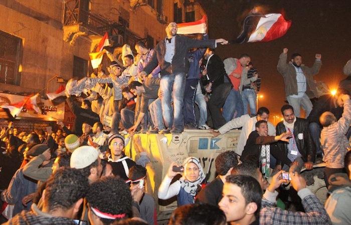アラブの春、ムバラク大統領の退陣後、軍の装甲車に上がって喜び合う市民たち=2011年2月11日、エジプト・カイロのタハリール広場