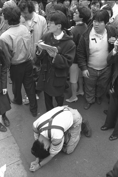 国公立大学の前期日程の合格発表で合格者名簿に名前がなく、地面にうずくまる1浪の受験生=1990年3月10日、東京都文京区の東大