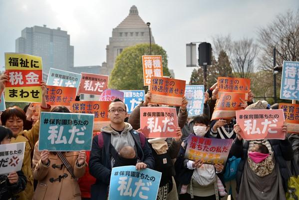 「保育園落ちたのは私だ」などと書かれた紙を掲げて立つ人たち=2016年3月5日、東京都千代田区の国会議事堂前