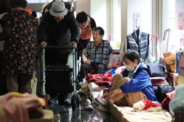 避難所になっている総合体育館で、アリーナに入れず廊下で避難生活を送る人たち=24日午前11時52分、熊本県益城町2016年4月24日