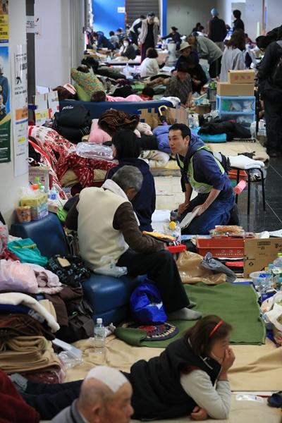 避難所になっている総合体育館でアリーナに入れず、廊下で避難生活を送る人たち=2016年4月24日、熊本県益城町