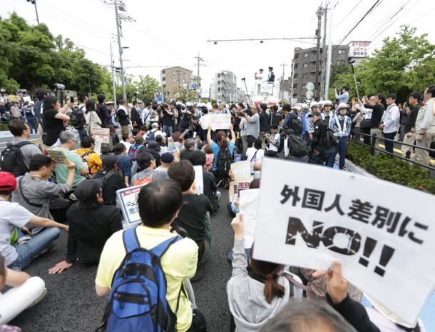 ヘイトスピーチのデモ会場で、デモを阻止しようとプラカードなどを掲げて座り込む人たち=6月5日、川崎市中原区