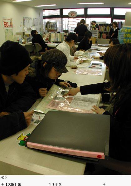 引っ越しシーズンに不動産店で賃貸住宅の物件を熱心に探す若者ら=2004年2月、京都市下京区