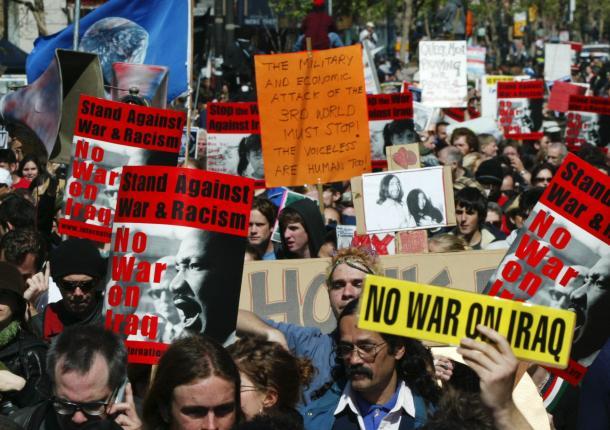 故キング牧師の写真などを掲げ、反戦を訴える人々=2003年3月20日、サンフランシスコ