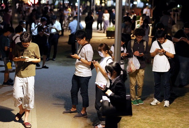 深夜にもかかわらず「ポケモンGO」に熱中する人たち=2016年7月28日、東京都墨田区の錦糸公園