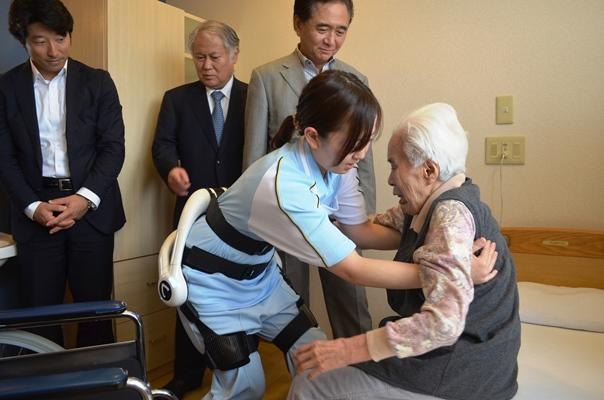 「ロボットスーツHAL」を装着して、入居者を車いすからベッドに移す介護士=2015年6月12日、横浜市港南区