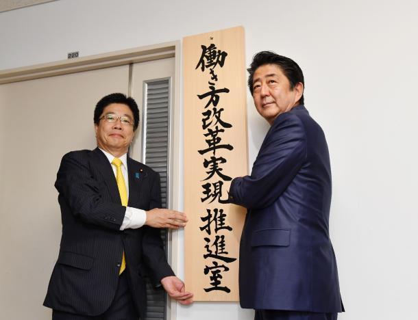 「働き方改革実現推進室」の看板をかかげる安倍晋三首相(右)と加藤勝信・1億総活躍担当相=9月2日、代表撮影