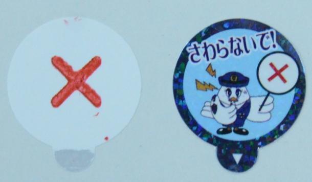 「さわらないで!」と書かれたシール(右)の1枚目をめくると、下から赤い「×」印が現れる