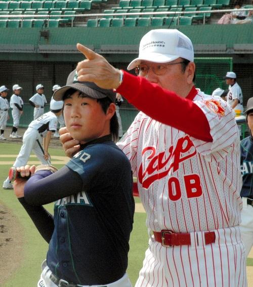 振り切ったあと顔を前に向けるよう指導する山本一義さん=2011年5月、山口市