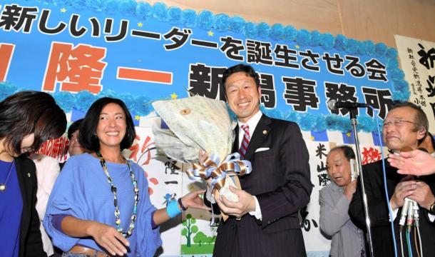 当選を確実にし、支持者から花束を受け取る米山隆一氏