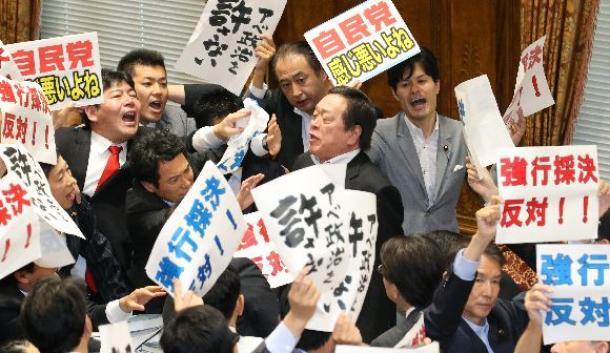 反対する野党銀に囲まれる中、安保関連法案の委員会採決をする浜田靖一委員長(中央右)=2015年7月15日