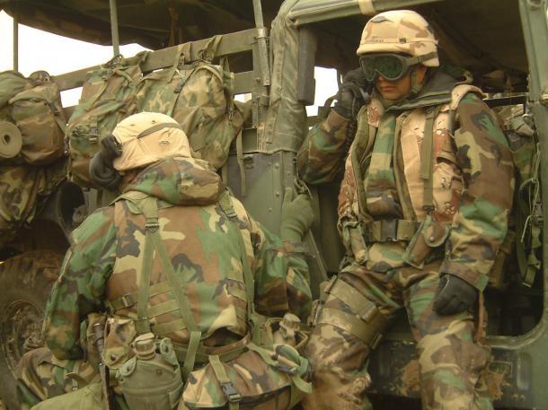 イラク軍から移動中に突然襲撃を受け、無線で近隣の部隊の状況を確認する米海兵隊員=2003年4月、イラク中部ナーシリア