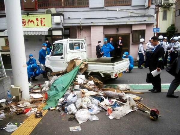 事故を起こした軽トラックは横転し荷台の物品が道路上に散乱した=2016年10月28日、横浜市港南区、周辺住民提供