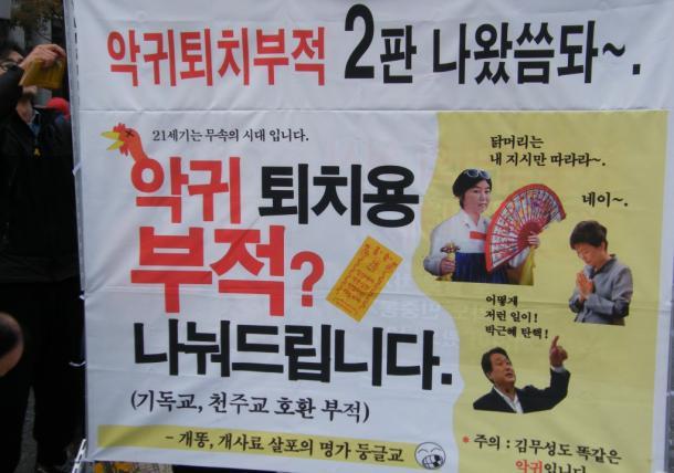 ソウルでの抗議集会で登場した、朴槿恵大統領とチェ・スンシル被告、与党セヌリ党「非朴派」の金武星前党代表をまとめて批判したポスター20161203