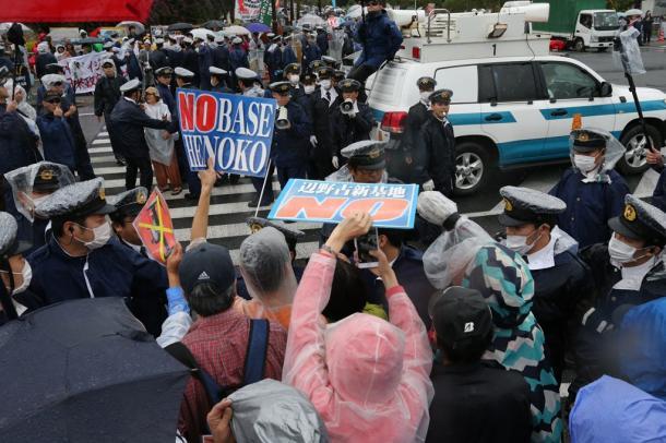 北部訓練場返還式が行われる会場へと向かう交差点で抗議活動をする人たち=22日午後3時50分、沖縄県名護市