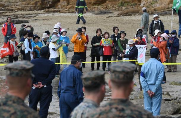た規制線から、大破した機体の方に向けて「オスプレイはいらない」などと気勢を上げる人たち=14日午後1時32分、沖縄県名護市安部