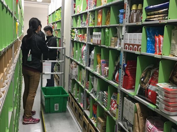 アマゾンの「プライムナウ」向け倉庫。注文された商品を作業員が一つずつ集めていく=東京都内