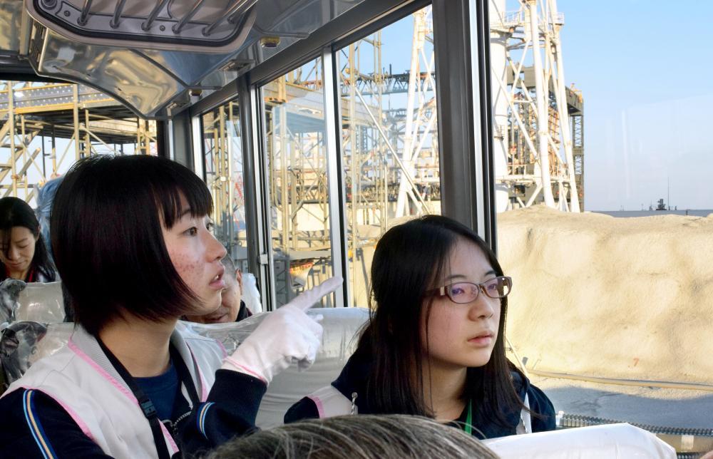 写真・図版 : 廃炉現場を見学する福島高校の生徒たち。後ろは水素爆発した1号機の原子炉建屋=2016年11月18日、川原千夏子撮影