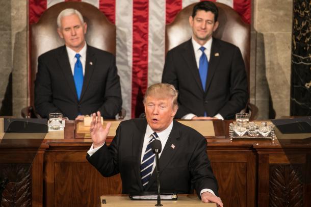 米連邦議会で演説をするトランプ大統領。後方にペンス副大統領(左)とライアン下院議長が座り、拍手を送りながら見守った=2月28日、ワシントン、ランハム裕子撮影