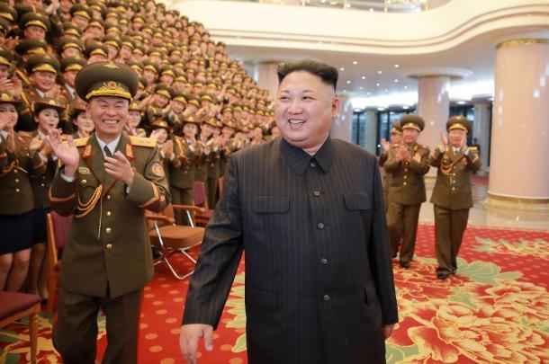 2月22日、平壌の人民劇場で創立70周年記念公演を行った功勲国家合唱団員との記念撮影場で歓迎を受ける金正恩・朝鮮労働党委員長。朝鮮中央通信が報じた=朝鮮通信