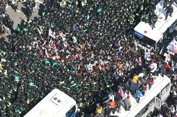 韓国憲法裁判所の決定に不満を持ち、警官隊と争う市民ら=東亜日報提供