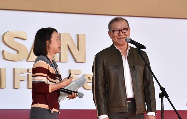 釜山国際映画祭の舞台あいさつに立った國村隼(右)=2016年10月9日、韓国・釜山