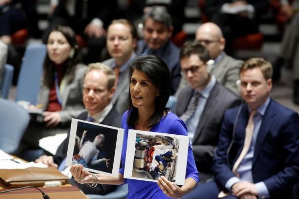 国連安全保障理事会の緊急会合で、幼児が横たわる写真を掲げて「行動」を求める米国のヘイリー国連大使=国連提供 UN PhotoEvan Sc