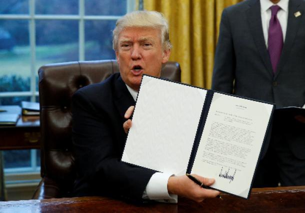 米ホワイトハウスで1月23日、署名した環太平洋経済連携協定(TPP)から離脱するための大統領令を見せるトランプ大統領=ロイター