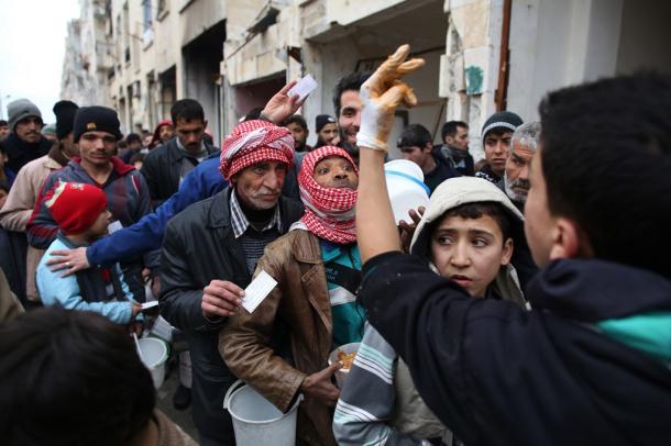 アレッポ東部のマサケン・ハナノ地区で食料の配給を受ける人々が長蛇の列を作る。多くの集合住宅は激しく破壊されているが、避難所から移動してきた避難民が生活を始めていた=9日午後、アレッポ20170110