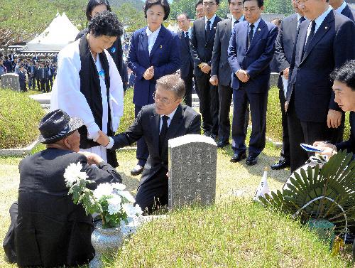 、1980年に軍が民主化を求める市民を武力制圧した光州事件の追悼行事で、墓地の前で遺族を慰問する文在寅大統領(中央)=ロイター.