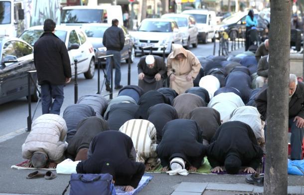 モスクを閉鎖され、抗議の意味も込め、路上で祈りを捧げるイスラム教徒の人たち=19日午後、パリ郊外クリシー市