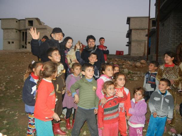 北イラクの難民キャンプにて。後列右手を上げているのが鎌田實さん。一人おいてJIM-NET事務局長の佐藤真紀さん