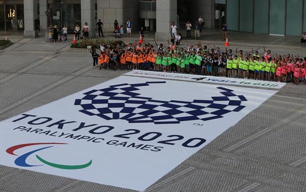 東京五輪のエンブレムからパラリンピックのエンブレムに作り替えるカウントダウンイベント=2016年8月25日、東京都新宿区の東京都庁