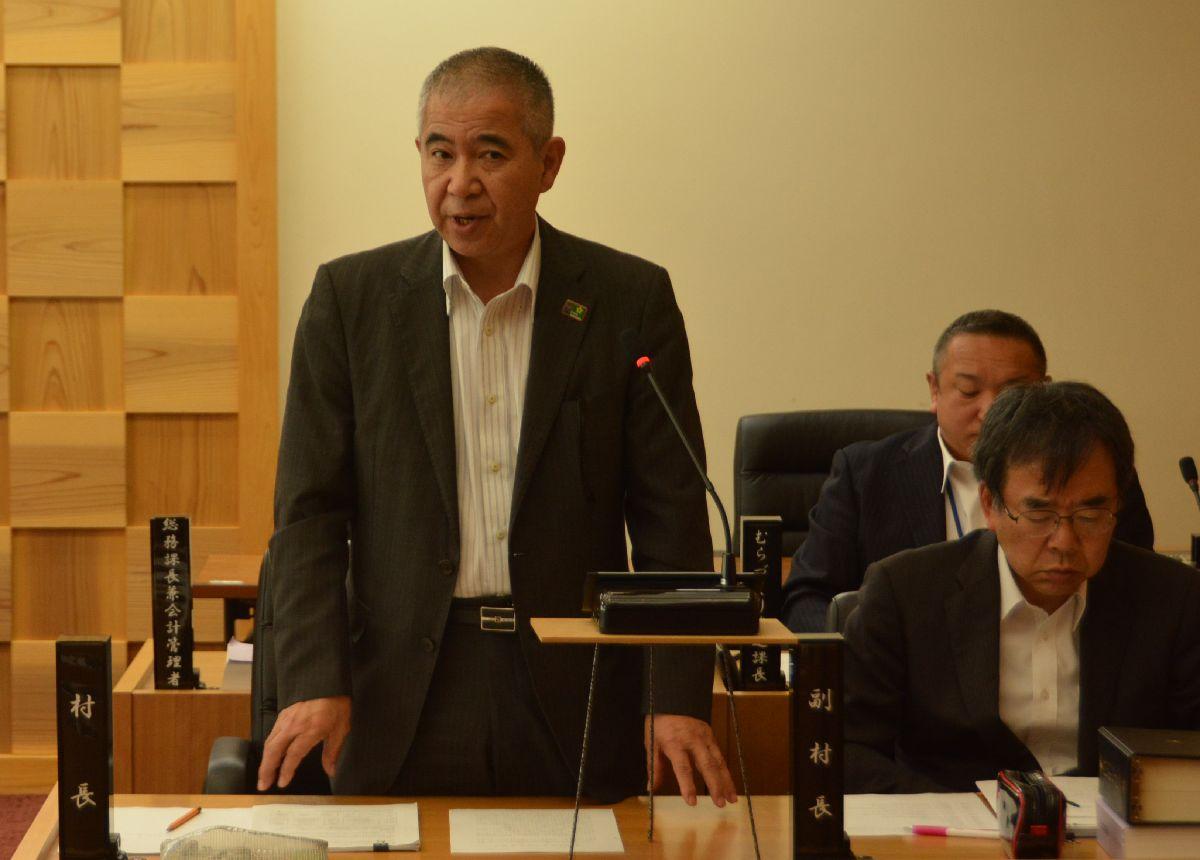 大川村村議会で町村総会の検討開始を表明する和田知士村長(左)