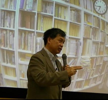 映画のために収集した膨大な書籍で埋められた書棚の画像を前に語る片渕監督